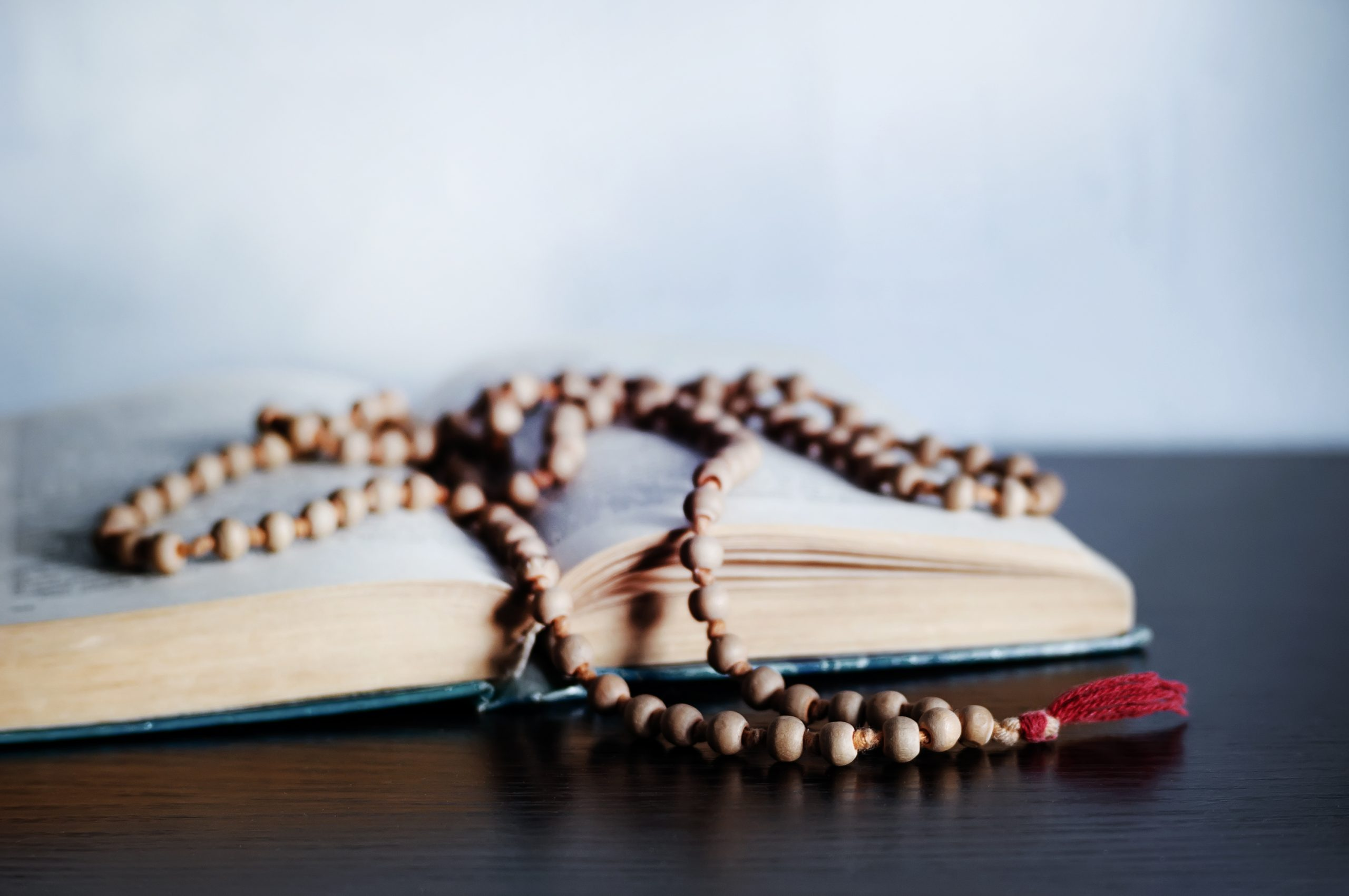 Old wooden rosary beads on a book of ceremonies. photo with copy space